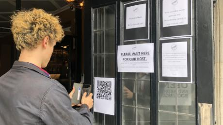A drinker scans a QR code in order to enter contact-tracing details before entering a south London pub.