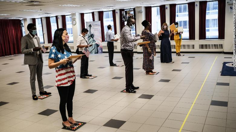 People are sworn in as new American citizens during a ceremony at the U.S. Citizenship and Immigration Services New York Field Office on July 2, 2020 in New York City. The ceremonies were brief and observed precautions, like wearing a mask and adhering to social distancing, to limit exposure to the coronavirus for those in attendance.