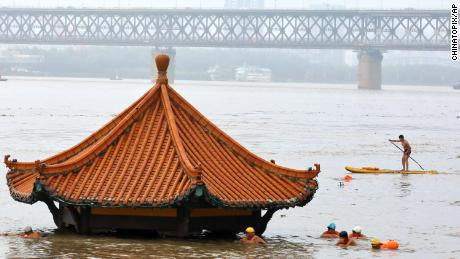 Residents swim in front of a pavilion by the river submerged by the flooded Yangtze River in Wuhan in central China's Hubei Province, July 8.