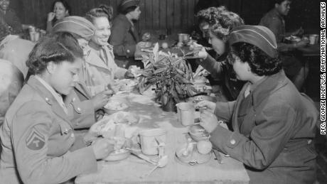 The women of the 6888th eat at a mess table in England.