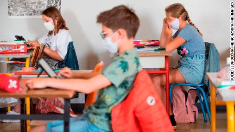 Pupils wearing cloth masks listen to their teacher at a school in Beaucamps-Ligny, near Lille, France.  Masks are now mandatory in all confined spaces.