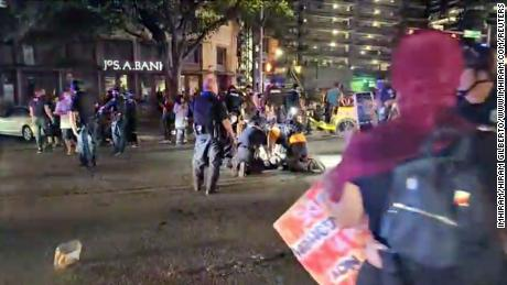 Police and protesters gather around a demonstrator who got shot after several shots were fired during a Black Lives Matter protest in downtown Austin, Texas, on July 25, 2020, in this screen grab obtained from a social media video.