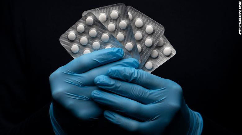 In this photo illustration a pack of Hydroxychloroquine Sulfate medication is held up.
