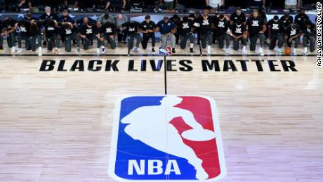 Coaches, referees, and members of the New Orleans Pelicans and Utah Jazz knelt together around the Black Lives Matter logo of the court during the national anthem before the start of Thursday's NBA basketball game in Lake Buena Vista, Fl.
