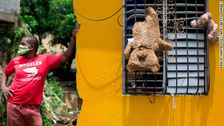 A man remains outside his home, where teddy bears hang from a window to dry after the passage of the storm throuth Hato Mayor, Dominican Republic, on July 31, 2020.