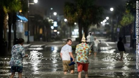 People walk through floodwaters Monday in Myrtle Beach, South Carolina.