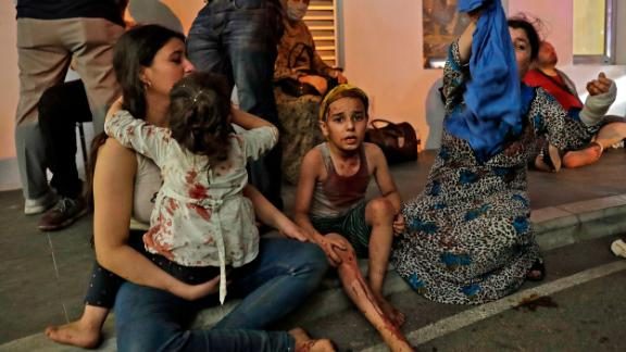 Wounded people wait to receive help outside a hospital. Emergency wards were inundated.