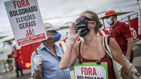 """A demonstrator holds a sign that reads """"Go Away Bolsonaro, General elections now!"""" during a rally against President Jair Bolsonaro and Governor of Rio de Janeiro Wilson Witzel amidst the coronavirus (COVID-19) pandemic at Copacabana beach on June 28, 2020 in Rio de Janeiro, Brazil."""