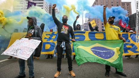 Demonstrators wearing face masks raise their fist on Paulista Avenue during a protest amidst the coronavirus (COVID-19) pandemic on June 14, 2020 in Sao Paulo, Brazil.