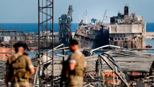 Lebanese soldiers stand guard in front of destroyed ships.