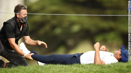 Koepka recieves treatment on the 12th hole during the second round of the 2020 PGA Championship.