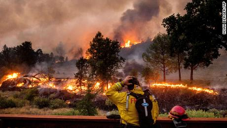 A firefighter rubs his head while watching the LNU Lightning Complex fires spread through the Berryessa Estates neighborhood of unincorporated Napa County, California, on Friday, August 21.