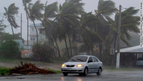 A car drives on a road as Tropical Storm Laura hits Guayama, Puerto Rico.