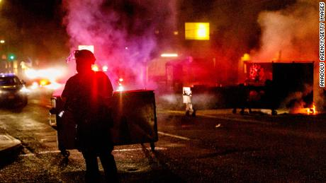 People protesting police brutality spray graffiti and start fires at the Portland Police Union on Friday.