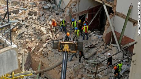 Rescue workers dig through the rubble of a badly damaged building in Lebanon's capital Beirut, in search of possible survivors.