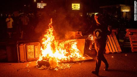 A protester passes a dumpster fire on Saturday, Sept. 5, 2020, during a demonstration in Portland.
