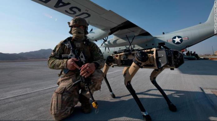 US Air Force Tech. Sgt. John Rodiguez provides security with a Ghost Robotics Vision 60 prototype during an exercises on Nellis Air Force Base in Nevada.
