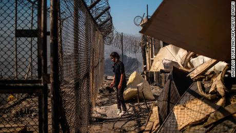 A young girl stands amid the rubble in the burnt out camp after the fires that Greek authorities believe were started by residents.