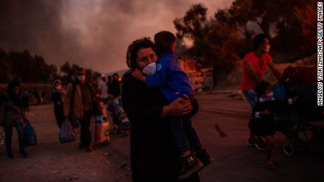 A woman takes a child after a fire breaks through a migrant camp on the Greek Aegean island.