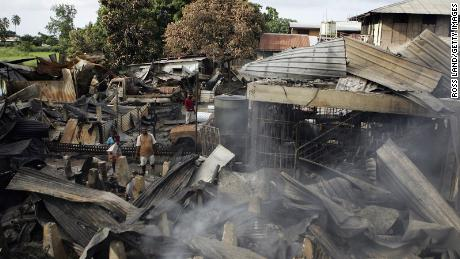 Locals search through the remains of smouldering buildings in Chinatown on April 21, 2006 following several days of rioting and looting in the Soloman Islands' capital, Honiara.