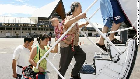 A mother and child board their flight as they are flown out of the  Solomon Islands on chartered aircraft provided by Beijing after losing all their possessions in the recent riots in Honiara, 23 April 2006.