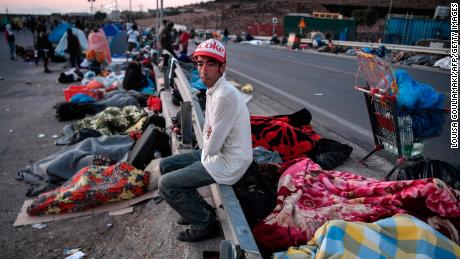 A man sits on a security fence as homeless migrants and refugees sleep on the side of the road after the fire.