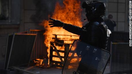 เจ้าหน้าที่ตำรวจปราบจราจลยืนอยู่ใกล้กองไฟระหว่างการประท้วงเสื้อกั๊กเหลืองในปารีสเมื่อวันที่ 12 กันยายน