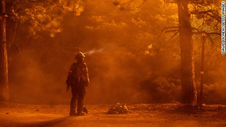 A firefighter watches flames near the Angeles Crest Highway at the Bobcat Fire north of Monrovia, California, on Friday.