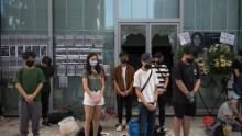 People stand in silent tribute at the Hong Kong Design Institute. Behind them, broken windows can be seen, the result of protests over an alleged lack of transparency regarding Chan's last movements.