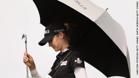 Nelly Korda จากสหรัฐอเมริกาหลบแดดขณะที่เธอเลือกไม้กอล์ฟจากกระเป๋าระหว่างการแข่งขันรอบสามที่ Mission Hills
