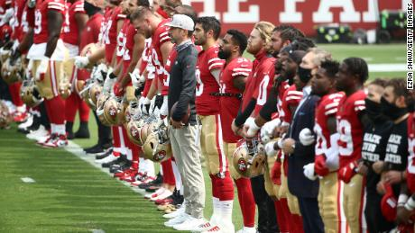 The San Francisco 49ers stand together during a presentation on social justice before their game against the Arizona Cardinals at Levi's Stadium on Sunday, September 13.