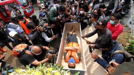 A man caught wearing a face mask in public is lying in a fake coffin, while members of the public and media take photographs by local authorities as part of the punishment and are enforced by local police in Jakarta on 3 September.