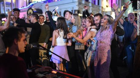 People are seen dancing to a busker in Leicester Square, central London, on September 12, days before social gatherings were restricted again.