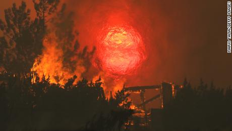 A home burns as the sun sets behind smoke and flames during the Bobcat Fire in Juniper Hills, California.