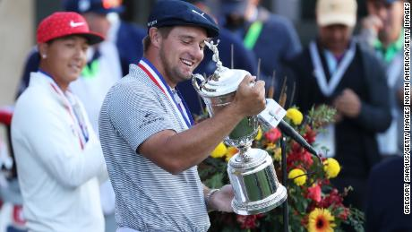 DeChambeau celebrates with the US Open championship trophy.