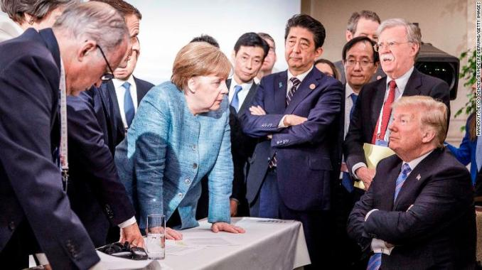 German Chancellor Angela Merkel, center, deliberating with US President Donald Trump, right, at the G7 summit on June 9, 2018 in Charlevoix, Canada.