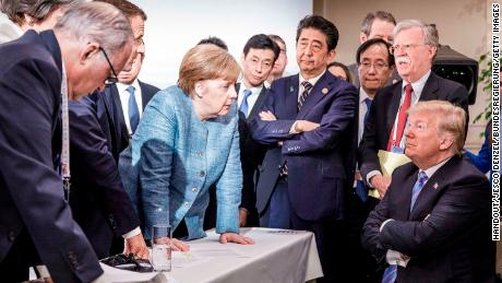 In this photo provided by the German Government Press Office, Merkel deliberates with Trump on the sidelines of the G7 summit in Charlevoix, Canada.