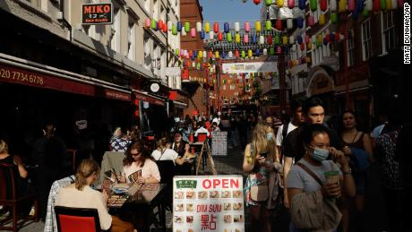 People sit outside in Chinatown, central London on Saturday.  The UK has introduced a 22 hour curfew for pubs and restaurants.