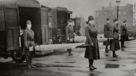 The St. Louis Red Cross Motor Corps was on duty with mask-wearing women holding stretchers at the backs of ambulances during the influenza epidemic in Missouri in October 1918.