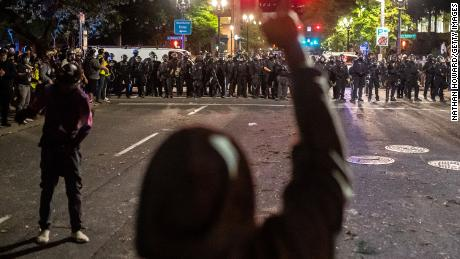 Protesters and police face off in Portland late Saturday.