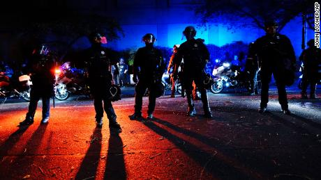 Police stand in a street during Saturday night's protests in Portland.