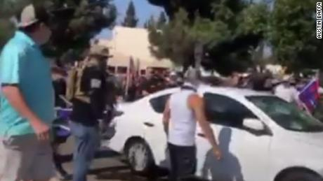 A car drives through a crowd of people at a protest in Yorba Linda, California.