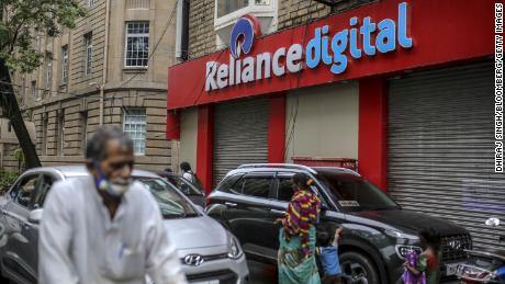 Pedestrians walking past a store of Reliance Digital Retail, a subsidiary of Reliance Industries, in Mumbai  in July.