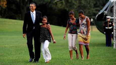 Barack and Michelle Obama return from vacation with daughters Sasha (left) and Malia in August 2010.
