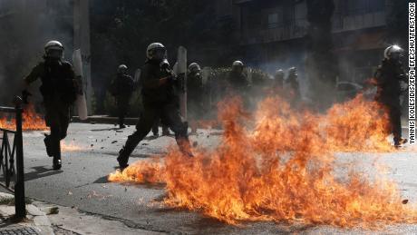 ตำรวจปราบจลาจลพยายามหลีกเลี่ยงเปลวไฟจากระเบิดน้ำมันที่ผู้ประท้วงขว้างเมื่อวันพุธ