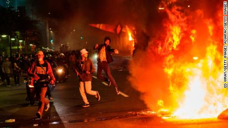 A protester throws a traffic cone onto a fire during Thursday in Jakarta.