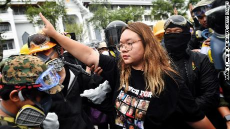 """Leader of the Opposition Panusaya """"Rung"""" Sithijiravattanakul (C) salutes the three-fingered Hunger Games during a pro-democracy rally in Bangkok on September 20, 2020."""