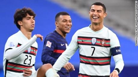 Ronaldo (right) shares a joke with French striker Kylian Mbappe (center) during the Nations League match in Portugal.
