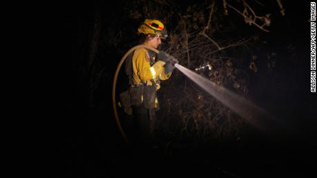 A fire fighter puts out hot spots from the Zogg Fire in Igo.