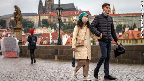 Tourists walk across Prague's medieval Charles Bridge as the Czech Republic faces a record spike after previously keeping numbers low.
